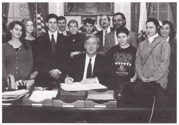 Gov Weld signs the Gay & Lesbian Student Rights Law (L to R) Emily Fishbein, Allison Bowen, Jamie Resnick, Paul Celucci, Chris Hannon, Marsian De Lellis, David LaFontaine, Rep. Byron Rushing, Sarah Lonberg-Lew, Anya Yankovich, and Phyllis Scattergood, 1993